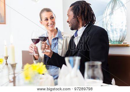 Business people, caucasian woman and african american man, toasting on deal with wine