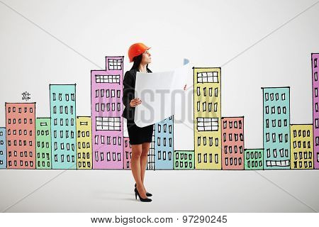 serious businesswoman in orange hardhat with blueprint looking up over background with variegated drawing houses