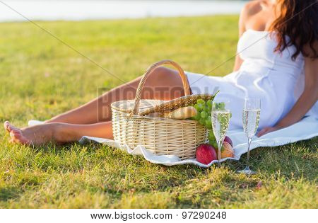 people, summer and holidays concept - close up of woman with food basket and champagne glasses on picnic