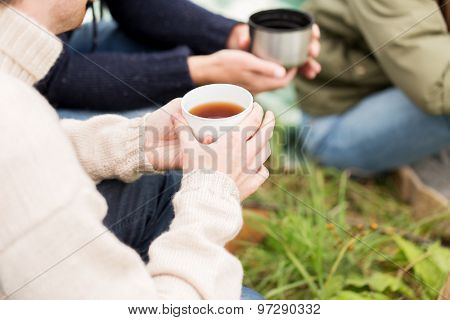 adventure, travel, tourism and people concept - close up of hikers drinking tea from cups at camp