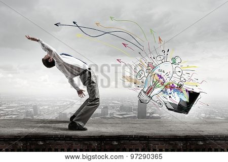 Balancing young man evading from explosion of ideas