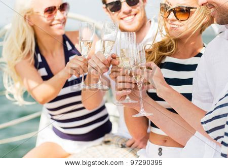 vacation, travel, sea, holidays and people concept - close up of happy friends clinking glasses of champagne and sailing on yacht
