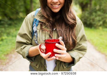 adventure, travel, tourism, hike and people concept - smiling young woman hiker with cup and backpack in forest