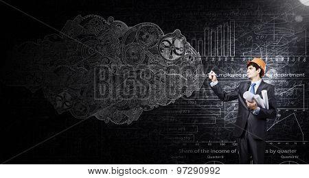 Engineer in helmet drawing gears on black wall