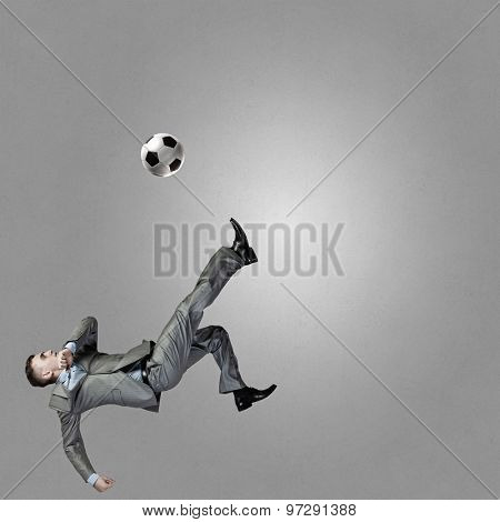 Businessman in suit hitting soccer ball in jump