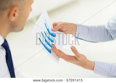 business, people, statistics and teamwork concept - close up of businessman hands showing chart to other man at office