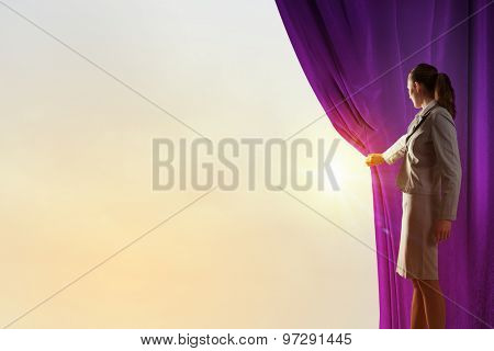 Young woman in business suit opening color curtain of stage