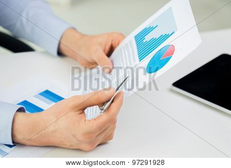 business, people and statistics concept - close up of businessman hands with chart and pen at office