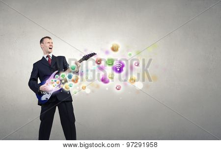 A young man in a black suit playing electric guitar