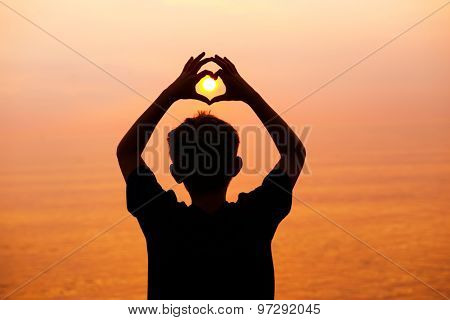 Boy on the beach making a heart shape with his hands at sunset. Main focus on head.