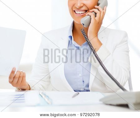 business, and communication concept - smiling african businesswoman with phone in office