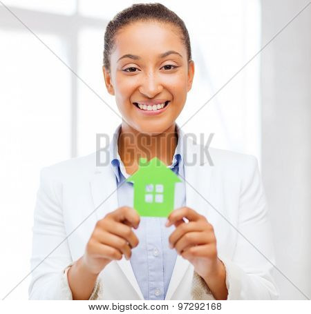 office, business, eco, power saving and real estate concept - african woman holding green paper house