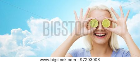 healthy eating, organic food, fruit diet, comic and people concept - happy woman having fun and covering her eyes with lime slices over blue sky and clouds background