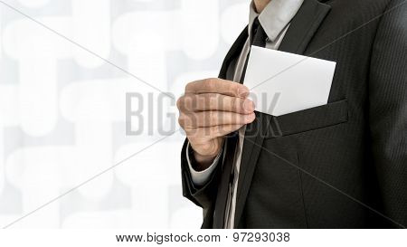 Businessman Removing Or Placing A Blank White Business Card In A Pocket Of His Suit Jacket