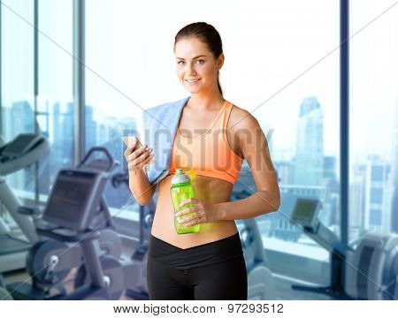 sport, fitness, technology and people concept - smiling sporty woman with smartphone, bottle of water and towel over gym machines background