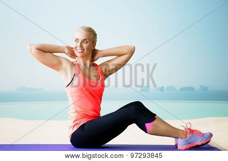 fitness, sport, exercising and people concept - smiling woman doing sit-up on mat over sea and pool at hotel resort background
