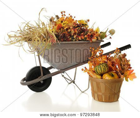 A rustic wheelbarrow full of colorful full foliage.  A basket with gourds and leaves sits nearby.  On a white background.