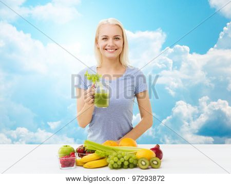 healthy eating, vegetarian food, diet, detox and people concept - smiling woman drinking green vegetable juice or shake from glass over blue sky and clouds background