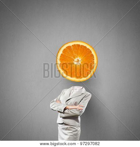 Headless businesswoman with orange instead of head