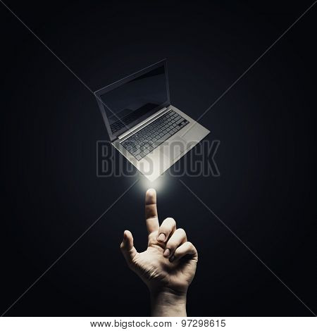 Male hand pointing with finger at laptop symbol