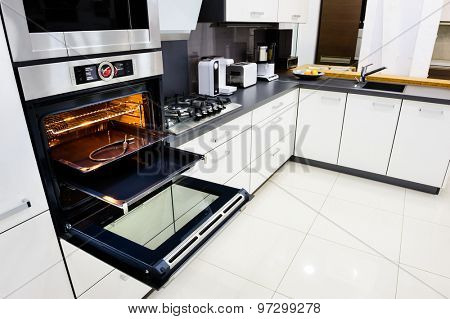 Modern luxury hi-tek black and white kitchen, clean interior design, focu at oven with open door