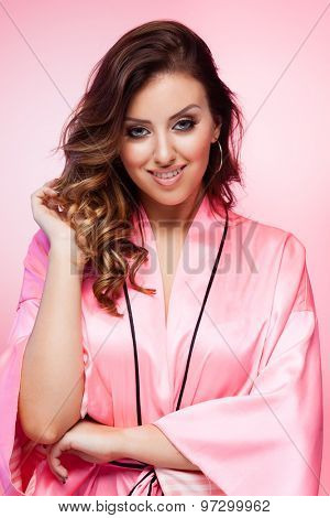 Young smiling brunette lady wearing a sexy bathrobe on pink background