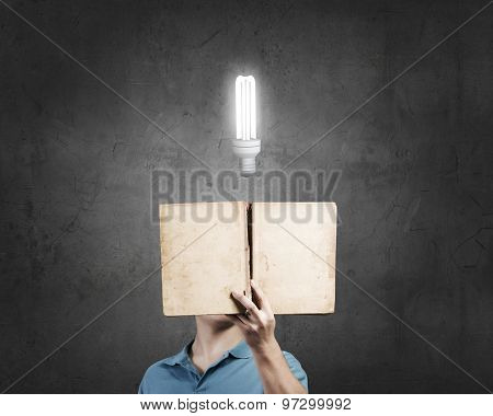 Businessman with light bulb instead of head and with opened book in hands