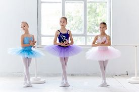 picture of ballet barre  - Three little ballet girls in multicolored tutu posing at ballet barre together in white studio - JPG