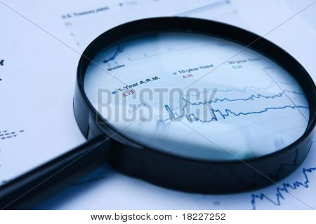 magnifying glass over financial newspaper