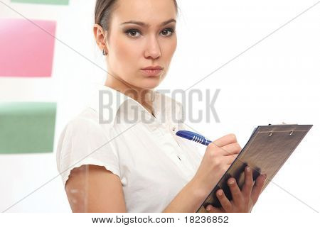 Happy pretty businesswoman pointing at adhesive notes on wall