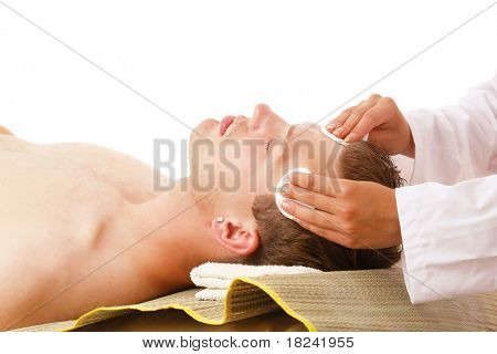Closeup of a man receiving facial massage from a woman