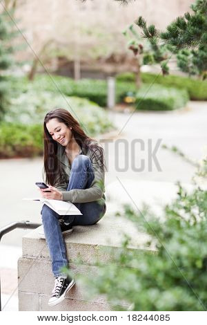 A shot of an ethnic college student texting on the phone at campus
