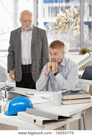 Scared young office worker man sitting at desk, angry senior executive standing.?