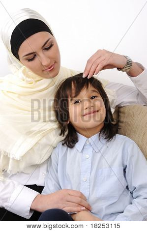Muslim arabic covered mother and son relaxing at the home
