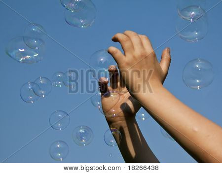 Hands catching bubbles against a blue sky