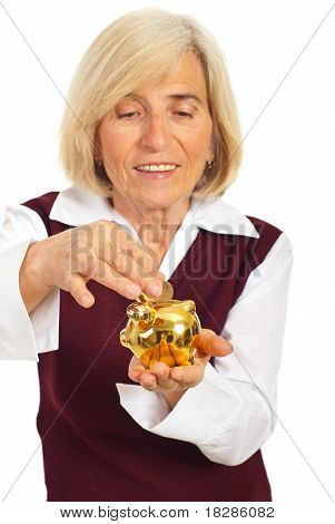 Senior Woman Saving Money In Piggybank