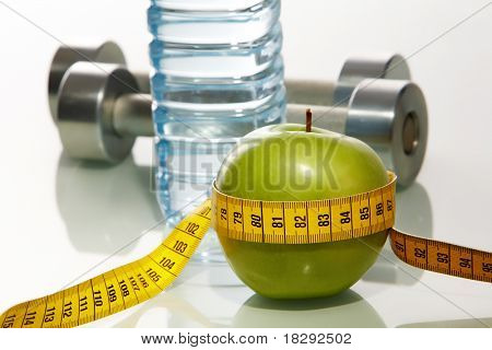 Close?up of green apple with measuring tape and two metal barbells on background