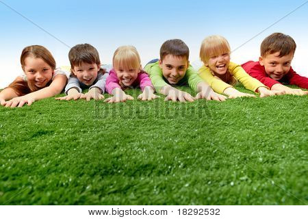 Group of happy children lying on a grass and stretching their arms