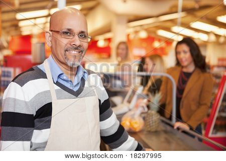 Portrait of a happy cashier with customer in the background