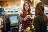 Image of smiling young lady standing in supermarket shop near cashiers desk holding credit card. Lo poster