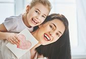 Happy mothers day! Child daughter congratulates mom and gives her postcard. Mum and girl smiling an poster