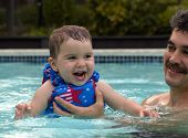 picture of swimming pool family  - A father watches as his toddler daughter emerges from the first dive of her life in a swimming pool with face slick with running water - JPG