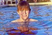 boy has fun swimming in the outdoor pool