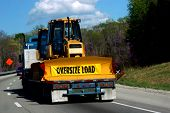 picture of oversize load  - flat bed semi hauls a bulldozer on the interstate - JPG