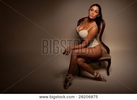 Dramatic Portrait Of Sexy Ballerina sitting sideways on a vintage chair facing towards camera and displaying large breasts and cleavage, dark background with ballerina highlighted,