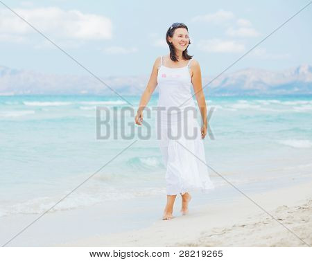 young woman walking near blue sea.