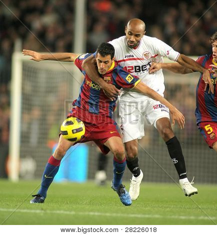 BARCELONA - OCT 30: Busquets(L) of Barcelona fight with Kanoute(R) of Sevilla during spanish league match between FC Barcelona and Sevilla at Nou Camp Stadium on October 30, 2010 in Barcelona, Spain