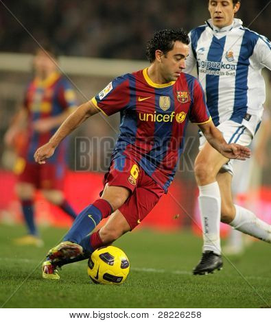 BARCELONA - DEC 12: Xavi Hernandez of Barcelona in action during a Spanish League match between FC Barcelona and Real Sociedad at the Nou Camp Stadium on December 12, 2010 in Barcelona, Spain