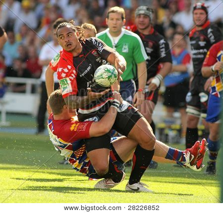 BARCELONA - APRIL 9: Toulons's Loamanu is tackled by Perpignan's player during the European Cup match between USAP Perpignan and RC Toulon at the Olympic Stadium in Barcelona, on April 9, 2011