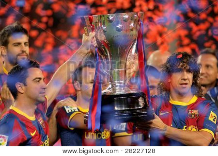 BARCELONA - MAY 15: Xavi and Carles Puyol of FC Barcelona hold the La Liga trophy after the match between Barcelona and Deportivo La Coruna at Camp Nou Stadium on May 15, 2011 in Barcelona, Spain